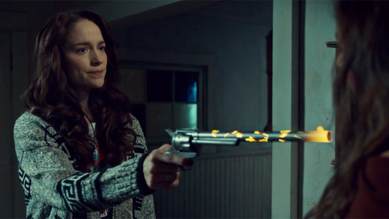 Wynonna points a glowing Peacemaker at Dark Waverly