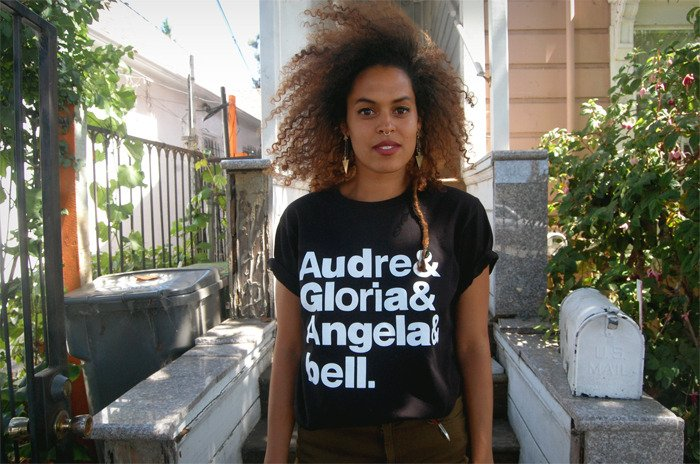 Black t-shirt with the stacked words in Helvetica-esque font: Audre & Gloria & Angela & bell.