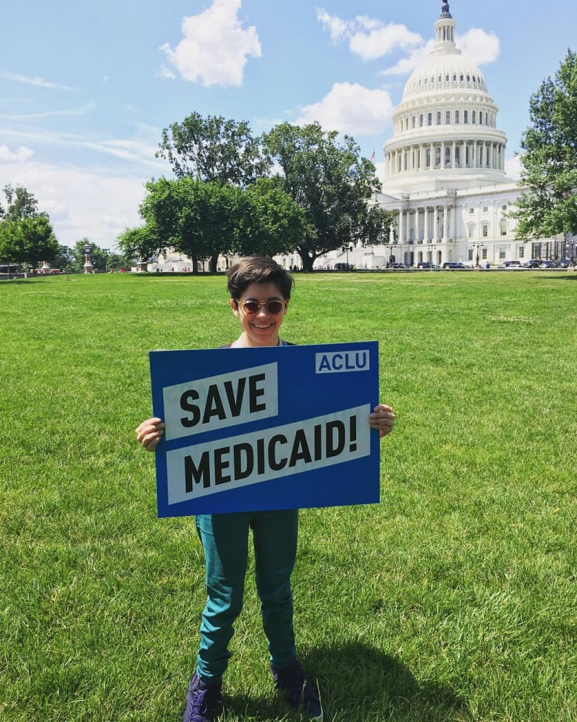 "A woman with short brown hair wearing sunglasses and teal jeans stands in front of the U.S. Capitol Building holding a blue and white sign that says ""Save Medicaid!""."