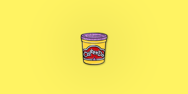 """Queerdo Enamel Pin / Description: Play-doh inspired pin with a glittery purple top, says """"queer-do"""" in the logo lockup / Metal: Black Enamel / Colors: Yellow, Red, White, Purple Glitter"""