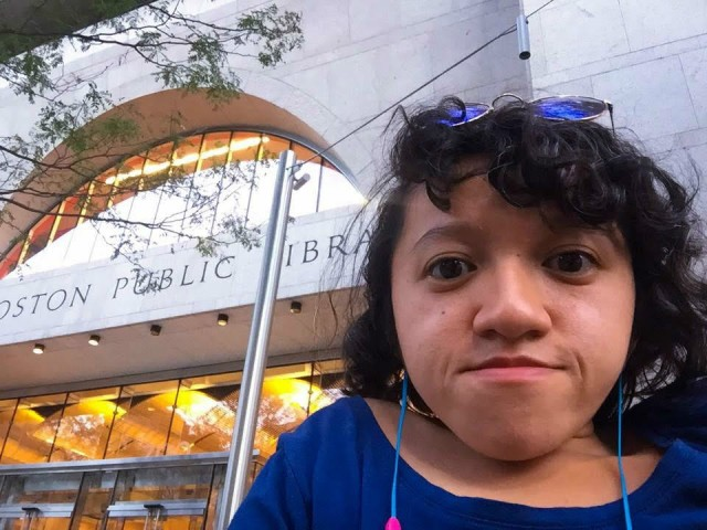 Sandy, a young Asian-American woman, poses for a selfie in front of the Boston Public Library