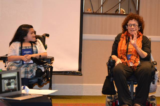 Sandy sits next to the author Simi Linton on stage at a conference. Sandy is on the left in a blue dress and white sweater, while Simi is on the right in all black except for an orange scarf around her neck.