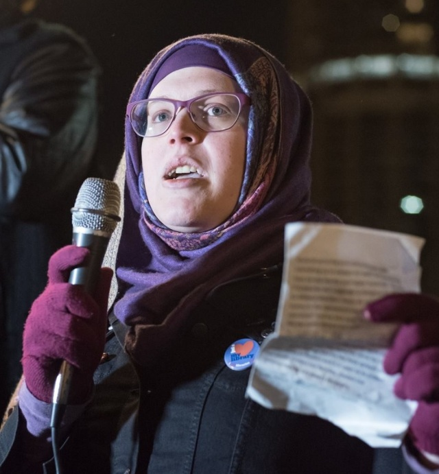 Mahdia Lynn in the process of giving a speech. She is wearing purple glasses, purple gloves, and a purple head scarf with a black coat, holding a microphone in one hand and a piece of paper in the other.