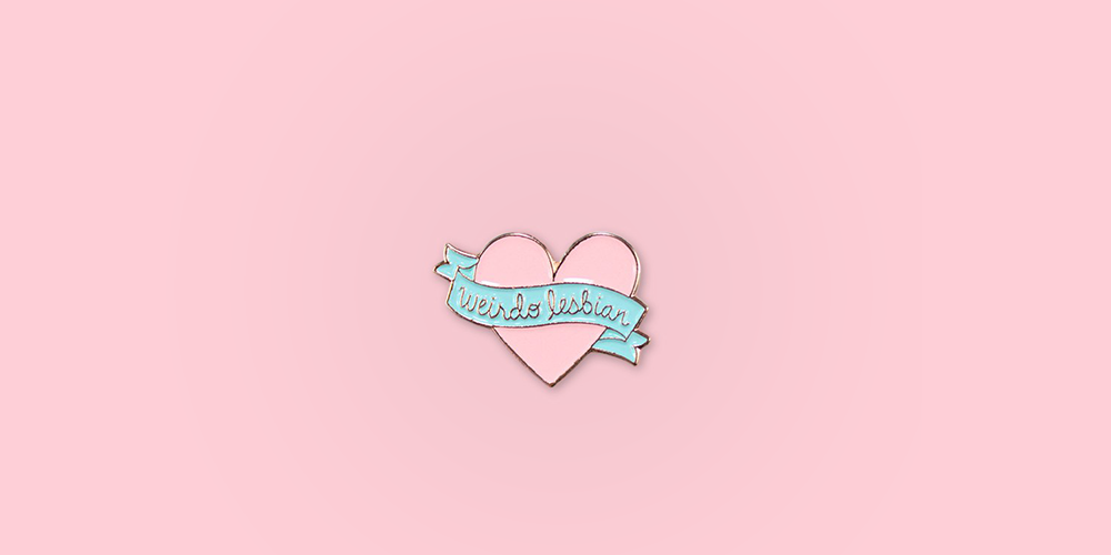 "Weirdo Lesbian Pin / Description: Heart with ribbon across center that says ""Weirdo Lesbian"" / Metal: Rose Gold / Enamel Colors: Pink and Mint"