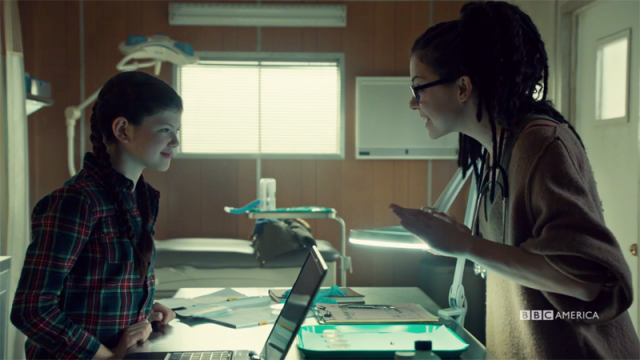 Cosima and Charlotte smile at.each other over a microscope