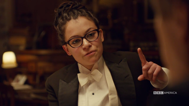 Cosima (still in her tux) holds up a finger mid-explanation