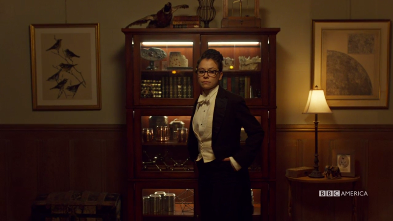 Cosima is standing in her tux with her hands in her pockets