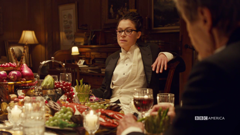 Cosima is leaning back in her tux looking like she owns the place