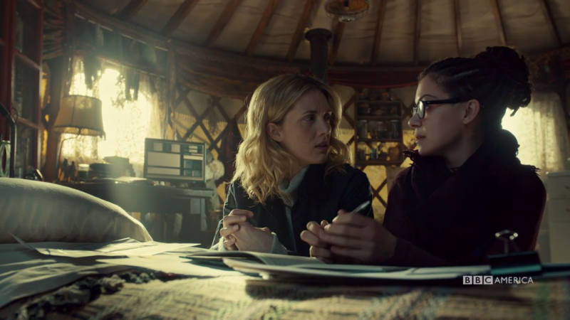Delphine and Cosima kneel by the bed to talk science