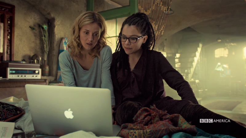 Cosima and Delphine sit together on the bed on their skype date just all casual and happy