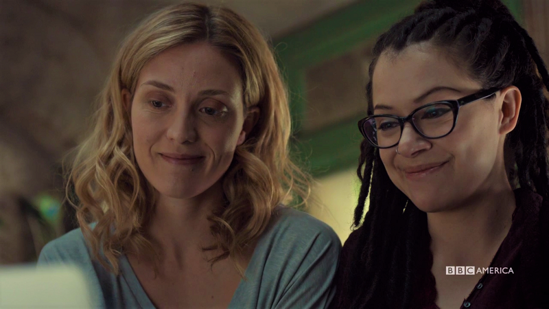 Delphine and Cosima smile at their computer with genuine happiness