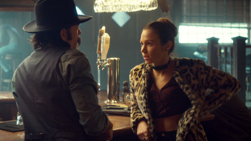 Waverly leans on the bar in her leopard coat talking to Doc in his cowboy hat