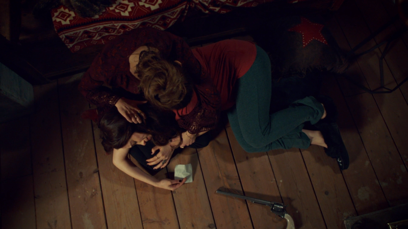 Wynonna cries on Waverly's lap with the note and Peacemaker nearby