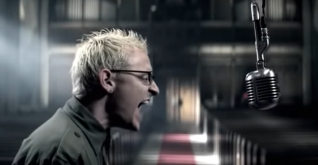 """Still from the official video for """"Numb"""",: showing Chester Bennington screaming into an overhead mic."""