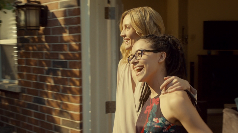 Cosima and Delphine enter the baby shower together, laughing