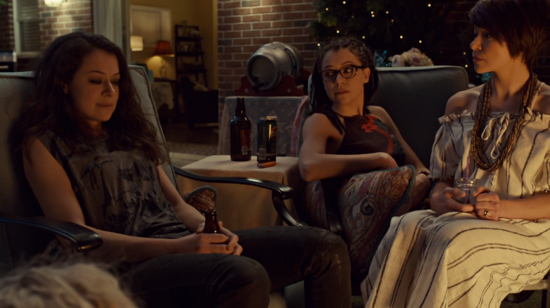 Sarah, Cosima and Alison sit together in the backyard (you can see the top of helena's head too)