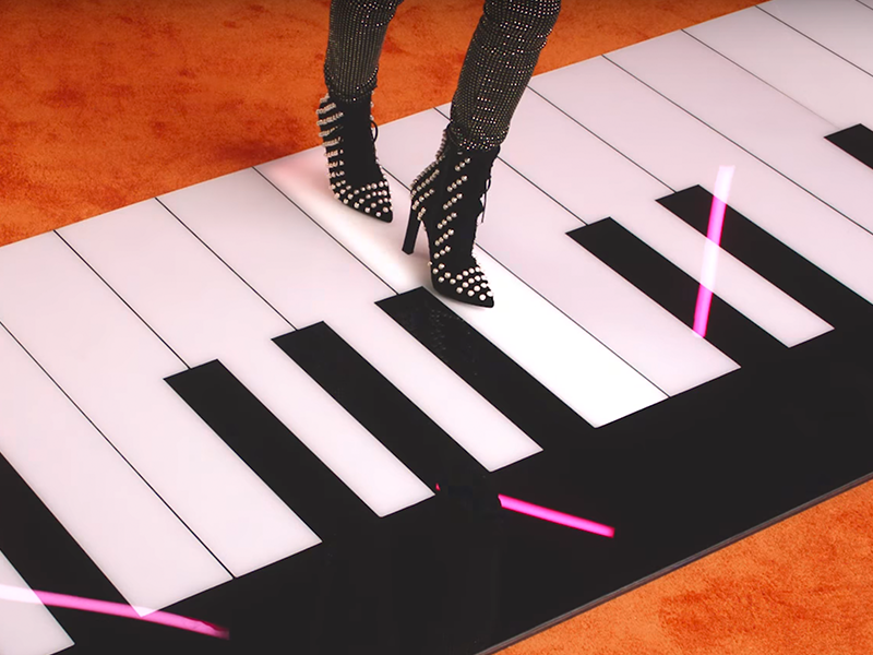 Feet playing a giant piano on the ground, in studded black heels.