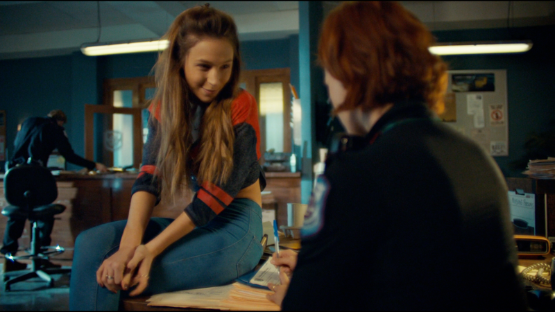 Waverly sits on Nicole's desk and smiles at her