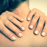A woman with light skin and long, dark hair massages her neck with her hands.