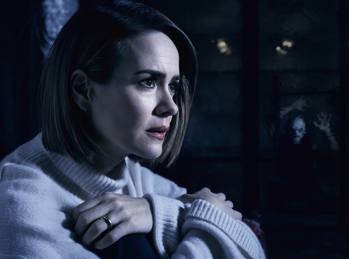 Sarah Paulson in a tasteful mock turtleneck, clutching at her chest with a concerned expression
