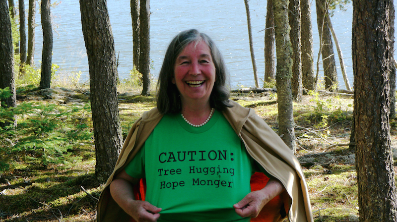 """an older white woman wearing a shirt that says """"CAUTION: Tree Hugging Hope Monger."""""""