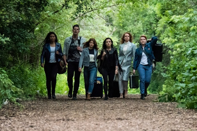 The cast of the Carmilla Move struts down a path in the forest