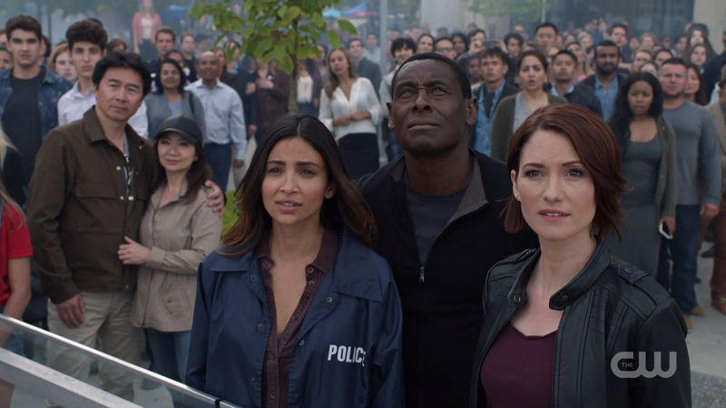Alex, Maggie and J'onn look up proudly at Supergirl saving the day