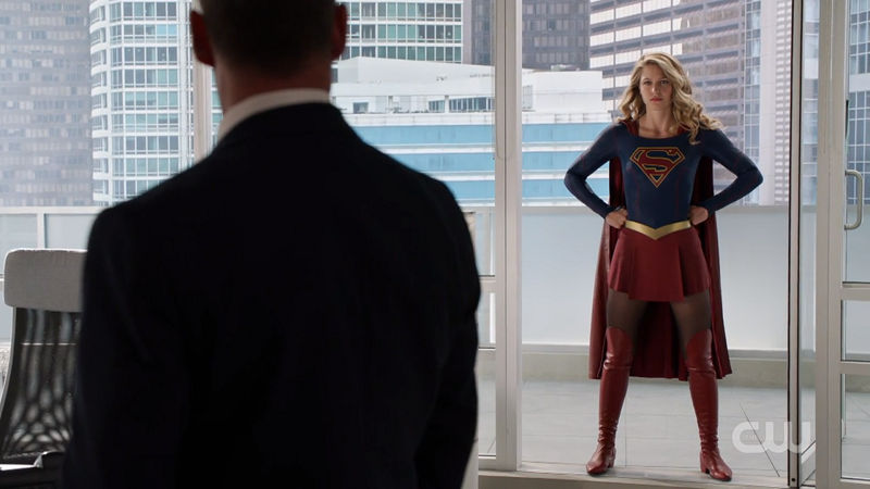 Supergirl does her stance in the balcony doorway