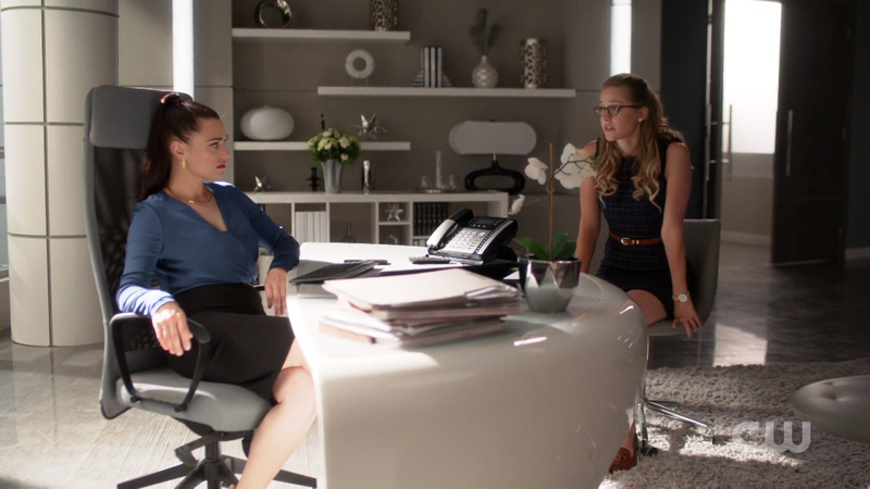 Lena slouches in her office chair and Kara sits across from her