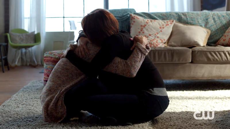 Alex and Kara hug while sitting
