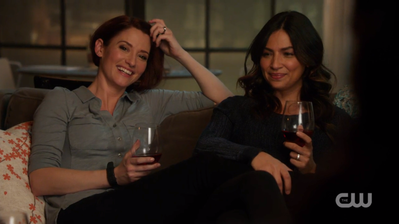 Alex and Maggie giggle on the couch.