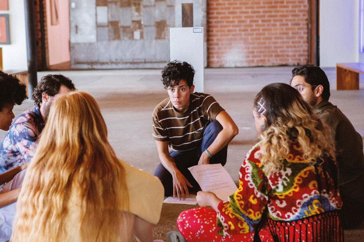 Image: An art gallery in Marfa. Devon, played by Roberta Colindrez, is presenting her play to a group of artists who are sitting in a semi-circle around her. She is wearing a brown t-shirt with white stripes and has dark, curly hair. One of her hands is on a piece of paper on the floor, the play script. Wee see the backs of five students circled around her.