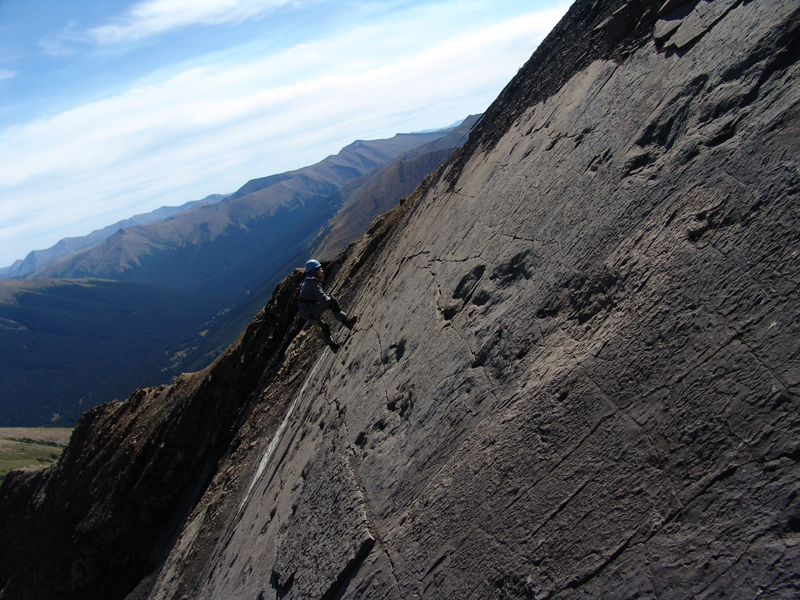 human on a steep incline with dinosaur prints