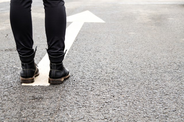 A person wearing black leggings and black boots stands on top of an arrow painted in the street, ready to walk forward.