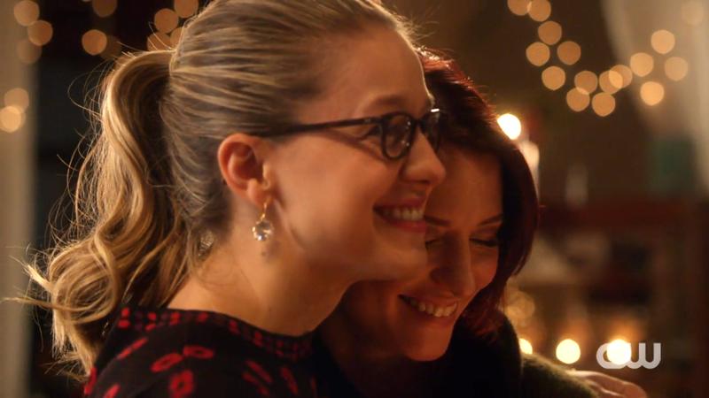 Kara and Alex giggle and hug