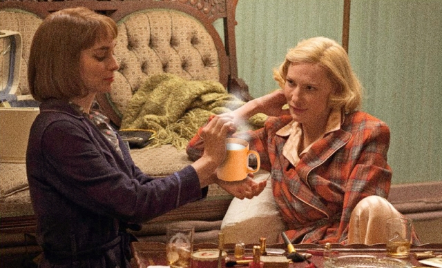 therese gives carol hot milk in an orange mug