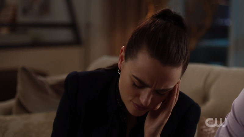 Lena holds her head and closes her eyes