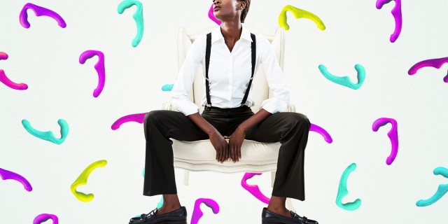 Colorful background of dildos, butch lesbian sitting on a chair casually in suspenders and a white button up shirt