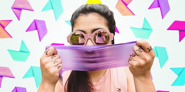 girl stretching a purple dental damn in front of her face, with a colorful background of folded up dental dams
