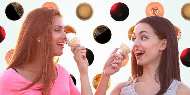 Two women pushing ice-cream cones on each other's noses and laughing, background is a pattern of various beverages