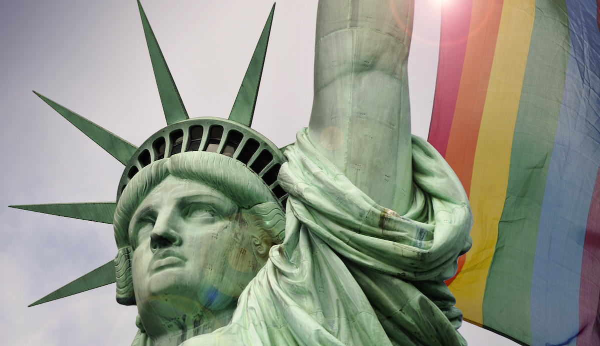 statue of liberty in front of a rainbow flag