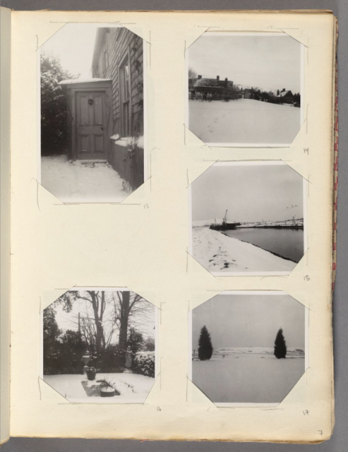 A page from an old photo album with five small black and white photos on it showing various winter landscapes (a door, a hillside with buildings, a marina, a field with two evergreen trees, a garden).