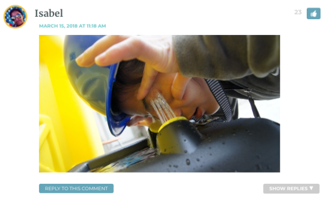 Photo of Isabel wearing a hard hat, washing her eyes out at a drinking fountain