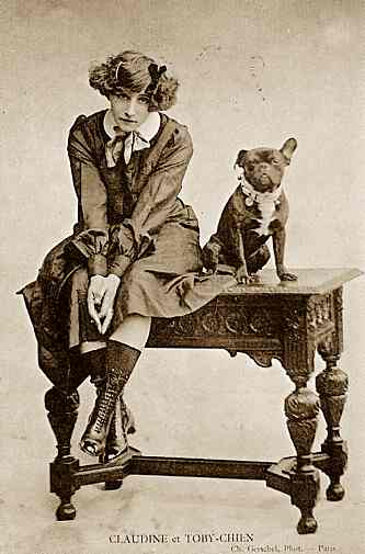 Colette and her bulldog Toby sit on a table together in a sepia-toned posed portrait