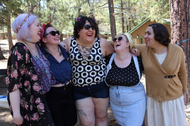 Group of five queer people with their arms around each other, laughing together
