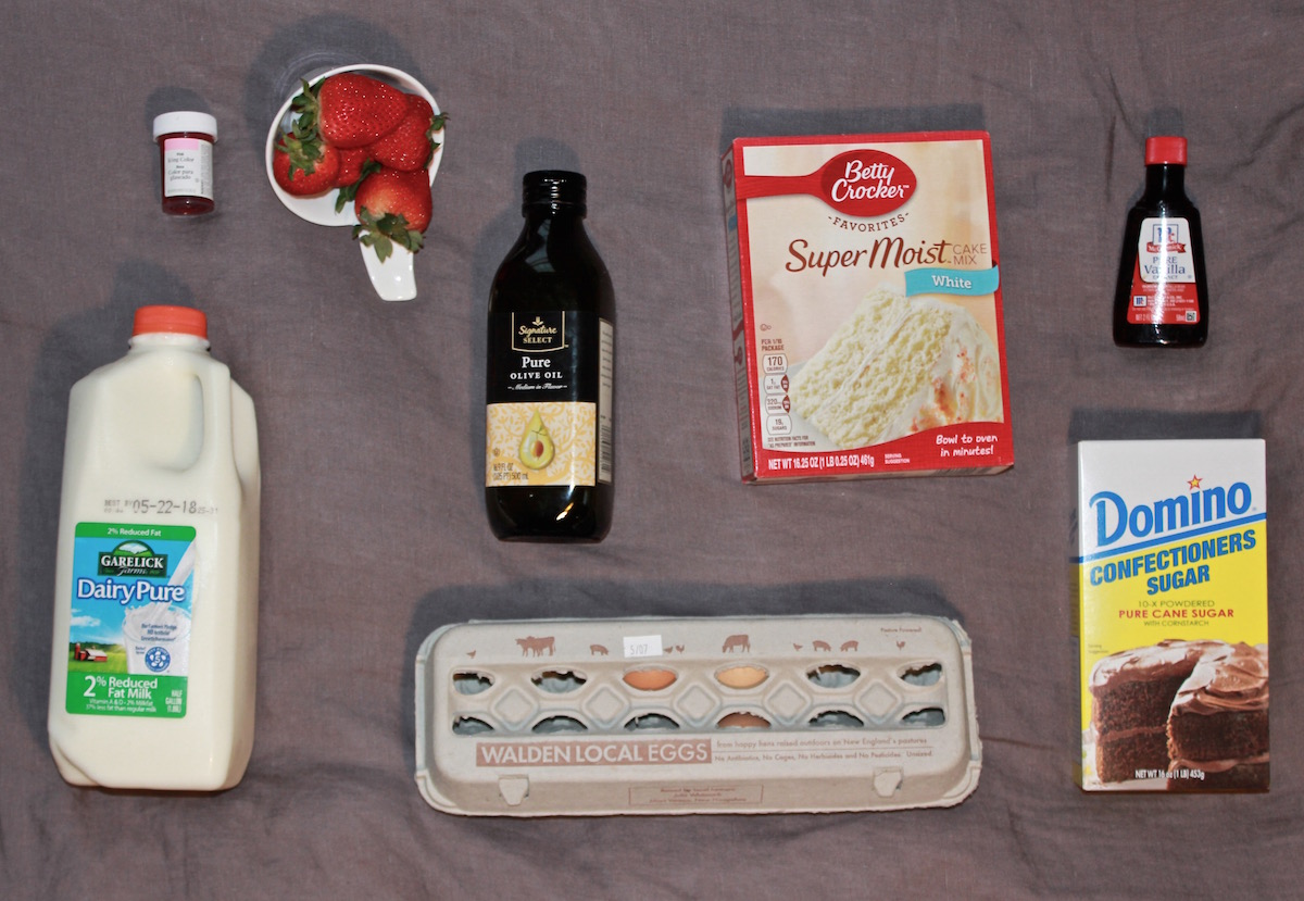 ingredients to make a cake (eggs, strawberries, box cake mix, etc)