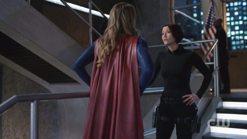 Supergirl has her hands on her hips, Alex has one hand on her hip one on the rail