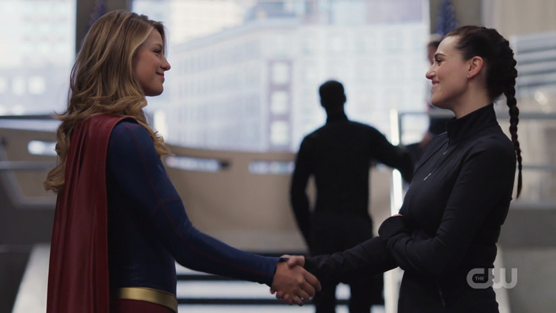 Supergirl and Lena Luthor shake hands while beaming at each other