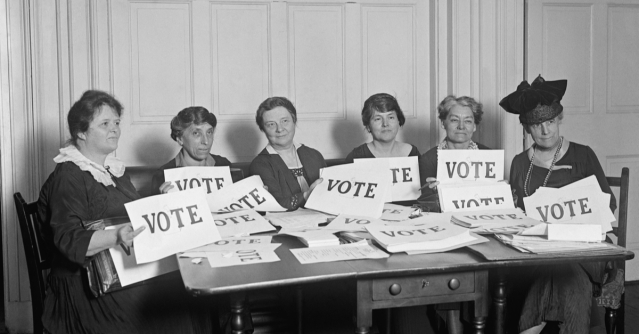 "Photo from 1924 of National League of Women Voters members holding up signs that say ""vote"""