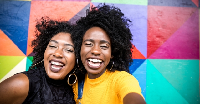 Black women smiling over a rainbow collage background